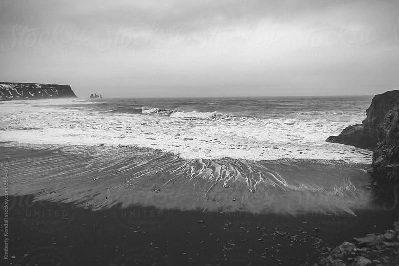 Black sand beach on a grey cloudy day by Kimberly Kendall for Stocksy United