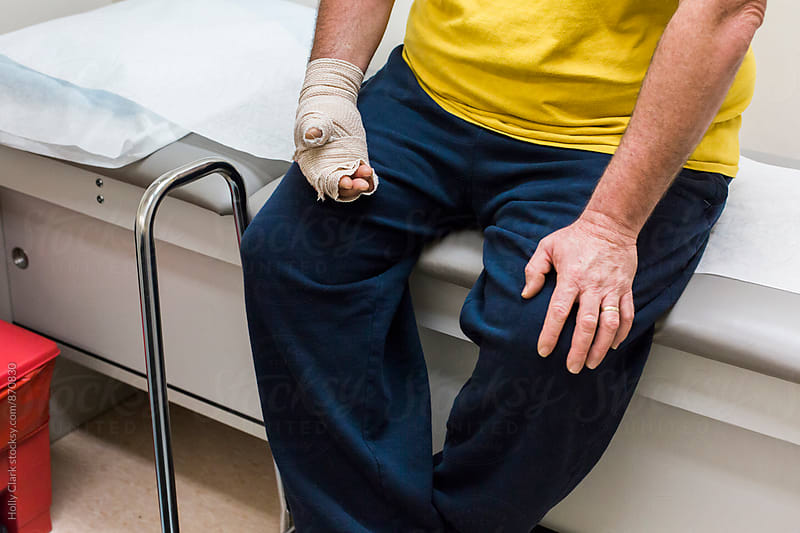 Man with bandaged hand sitting in doctor's office by Holly Clark for Stocksy United
