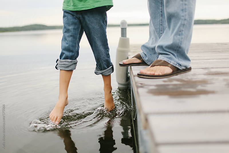 father dangles his son over water by Kelly Knox for Stocksy United