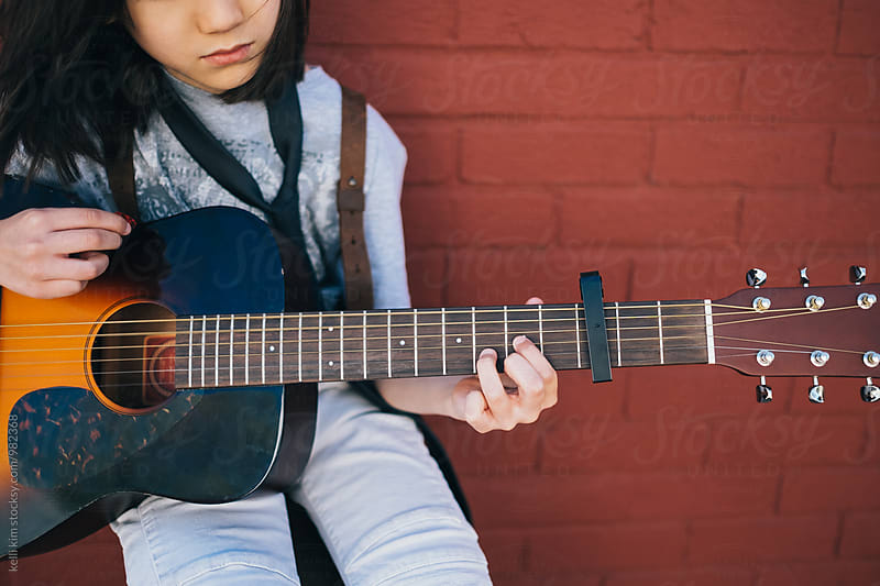 Young boy practicing on his acoustic guitar by kelli kim for Stocksy United