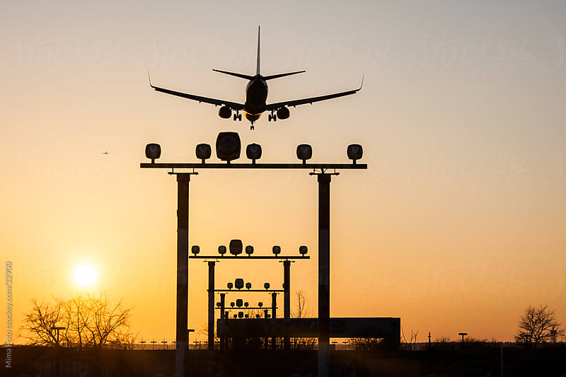 Airplane landing at sunset by Mima Foto for Stocksy United