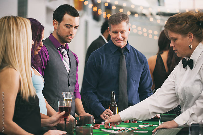 Casino: Group Of People Playing Blackjack At Table by Sean Locke for Stocksy United