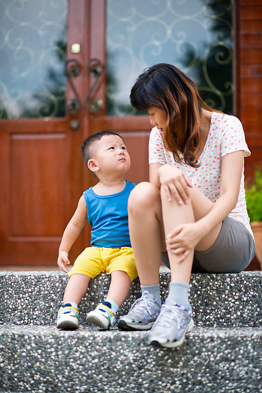 Mother and kid talking on stairs by Lawren Lu for Stocksy United