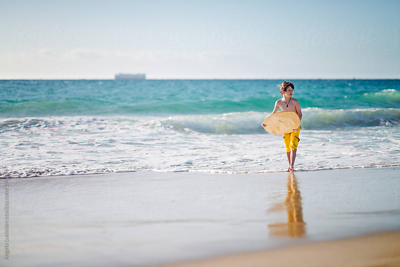 Boy looking for the next ride on a skim board at the beach by Angela Lumsden for Stocksy United
