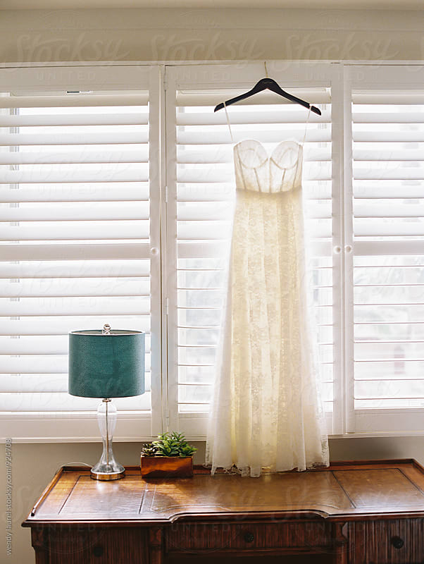wedding dress hanging in window with blue lamp by wendy laurel for Stocksy United