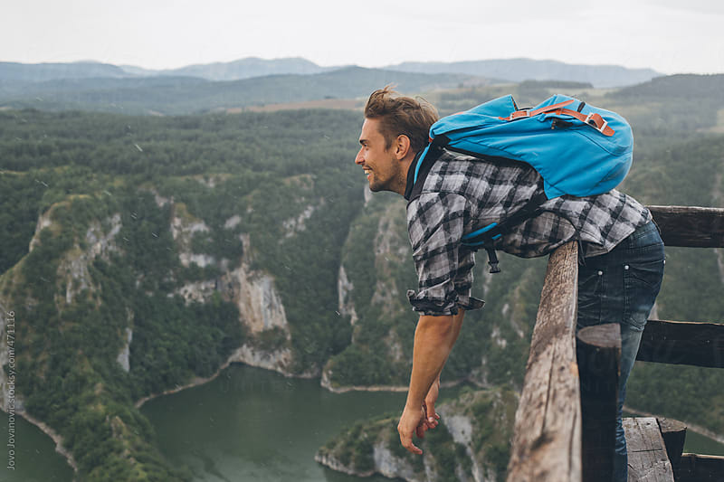 Young man leaning over the edge and of a viewpoint looking at mountains and lakes by Jovo Jovanovic for Stocksy United