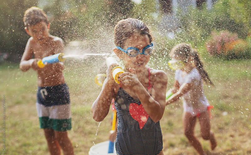 Children splashing with water guns. by Dejan Ristovski for Stocksy United
