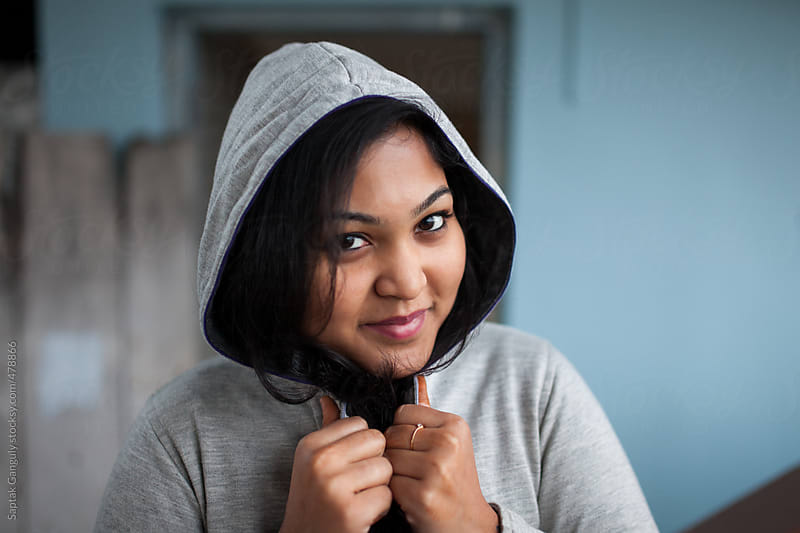 Beautiful girl in sweatshirt looking at camera and smiling,winter portrait by Saptak Ganguly for Stocksy United