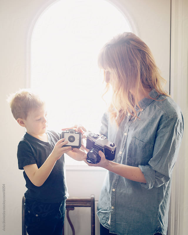 Mother showing son how to use a camera by Ania Boniecka for Stocksy United