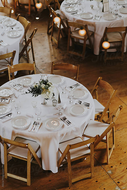 Wedding Reception Tables in Barn Reception Venue by Alicia Magnuson Photography for Stocksy United