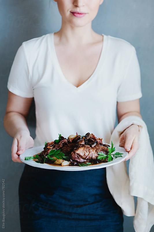 Woman holding a dish of Coq au vin  by Ellie Baygulov for Stocksy United