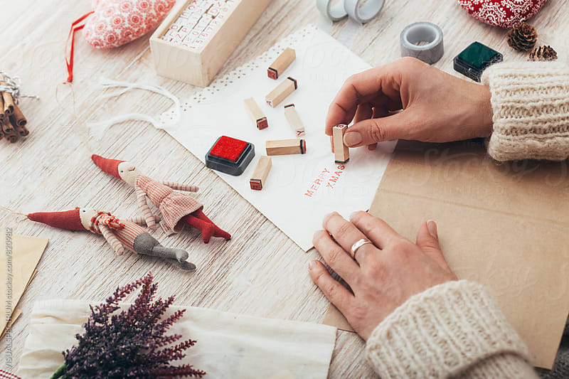 Christmas Holidays - Woman Using Stamp Letters to Write Merry Xmas on Pretty White Paper by Julien L. Balmer for Stocksy United