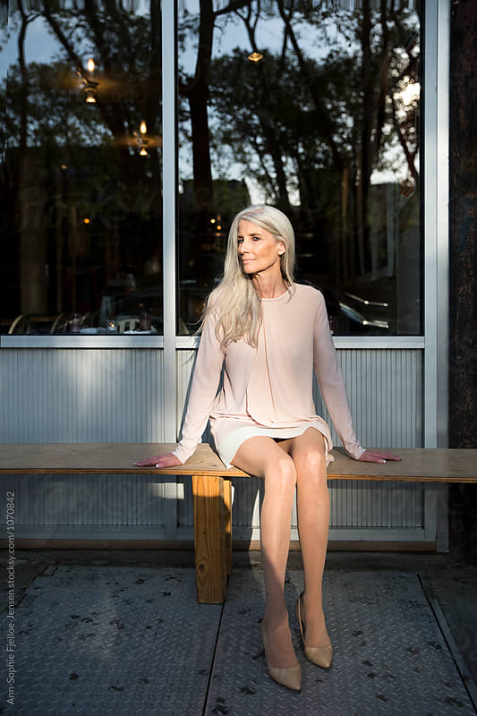 Woman sitting on a bench  by Ann-Sophie Fjelloe-Jensen for Stocksy United