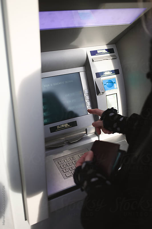Woman using an atm machine in Holland by Marcel for Stocksy United