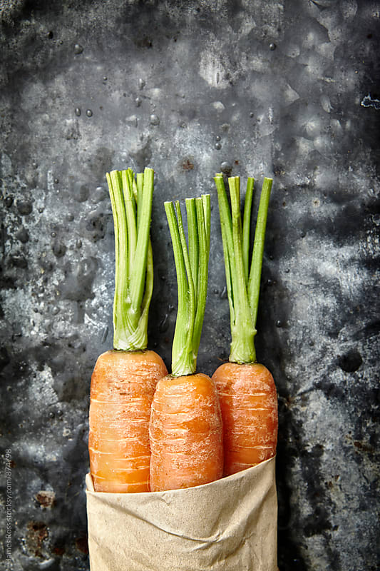 Three carrots with cut green tops by James Ross for Stocksy United