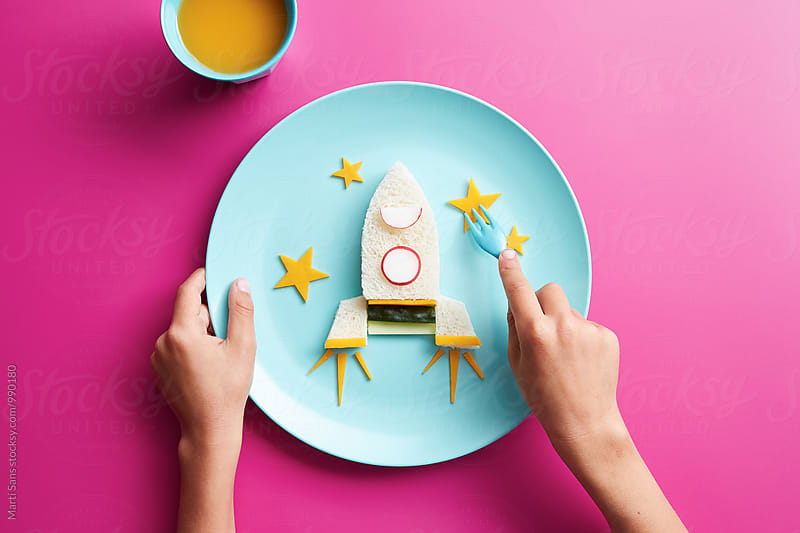 Unrecognizable kid eating spaceship omelette with vegetables by Martí Sans for Stocksy United