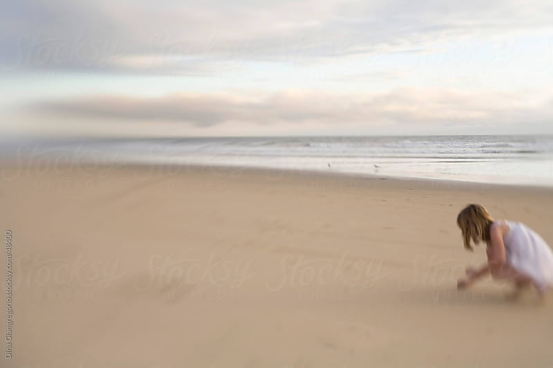 Girl wearing white dress on wide open beach kneeling while touching sand  by Dina Giangregorio for Stocksy United