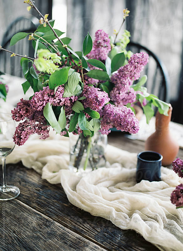 Lilac flower arrangement on a served table by Julia Kaptelova for Stocksy United