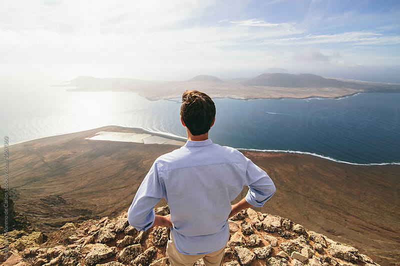 Back view of unrecognizable man looking at beautiful spaciousness landscape with sea and island by Alejandro Moreno de Carlos for Stocksy United