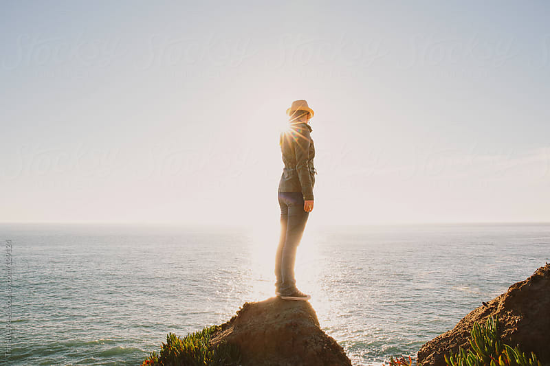 Woman standing on rock in nature looking out at ocean by Trinette Reed for Stocksy United