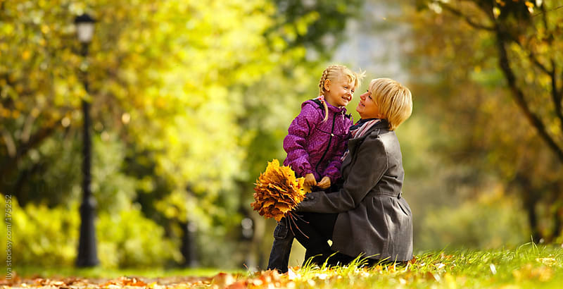 Mother and daughter playing in autumn park by Ilya for Stocksy United