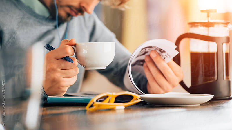 Man working through notes in cafe by Aila Images for Stocksy United