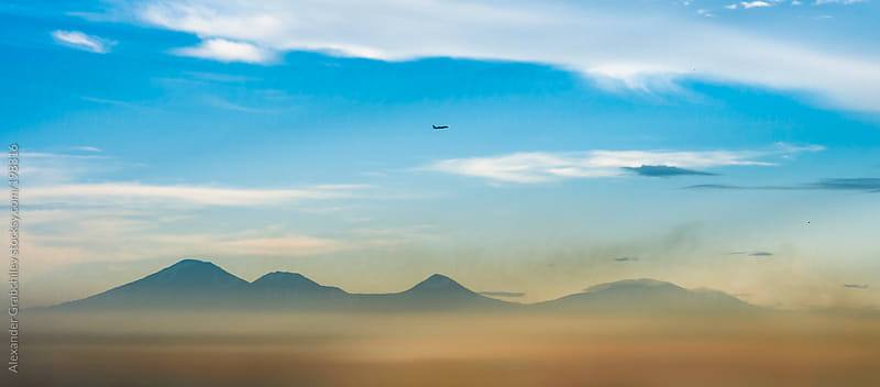 scenic view of  volcanic mountains & flying airplane by Alexander Grabchilev for Stocksy United