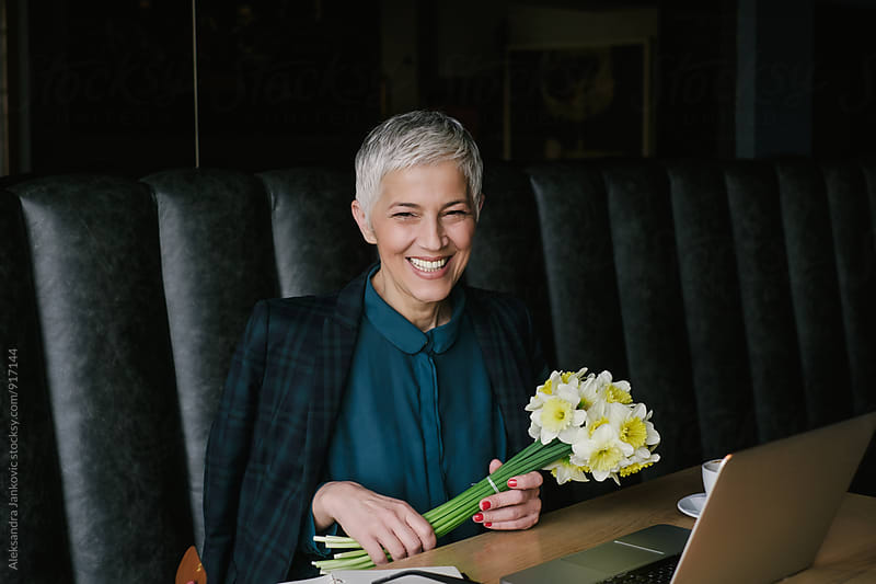 Smiling Senior Businesswoman Holding Bouquet by Aleksandra Jankovic for Stocksy United