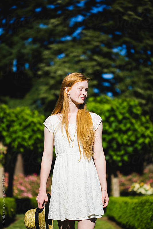 Beautiful young girl with long red hair walking in the park by michela ravasio for Stocksy United