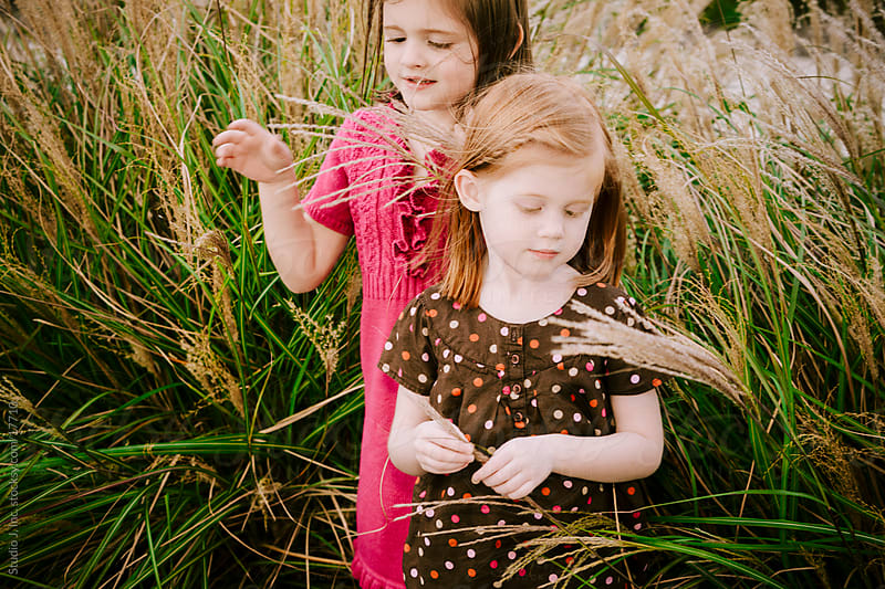 Little Girl Sisters in Tall Grass Outside by Jani Bryson for Stocksy United