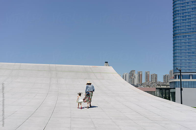 Mother and daughter running on a cement slope by MaaHoo Studio for Stocksy United