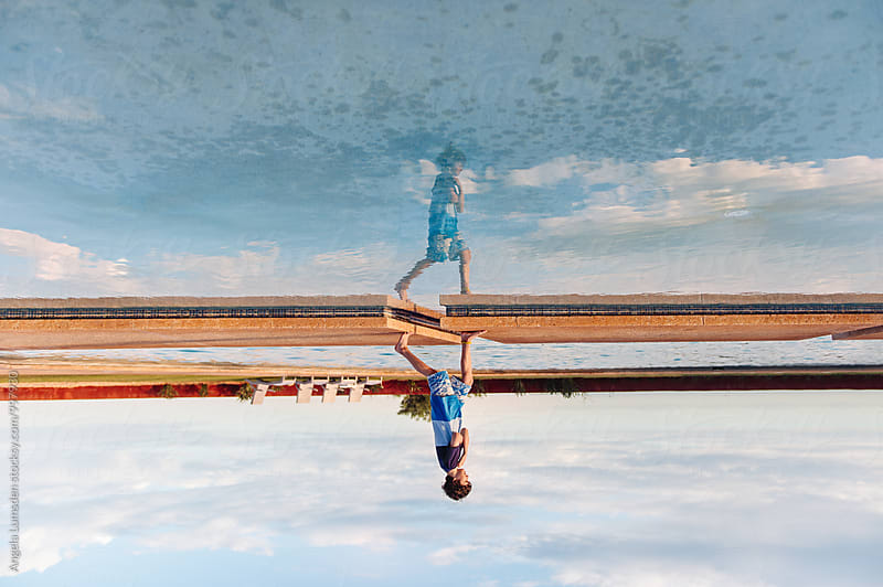 Boy and reflection running across a pool by Angela Lumsden for Stocksy United