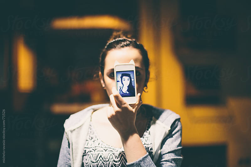 Girl holding her smart phone. by michela ravasio for Stocksy United