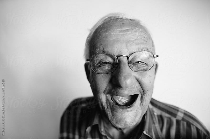 Playful senior man removing dentures and laughing by Rob and Julia Campbell for Stocksy United