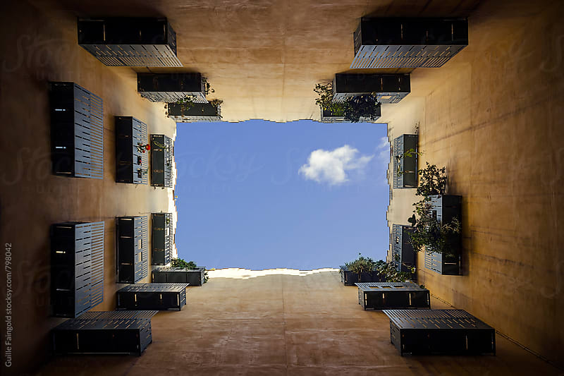from below: blue sky through the courtyard of a building by Guille Faingold for Stocksy United