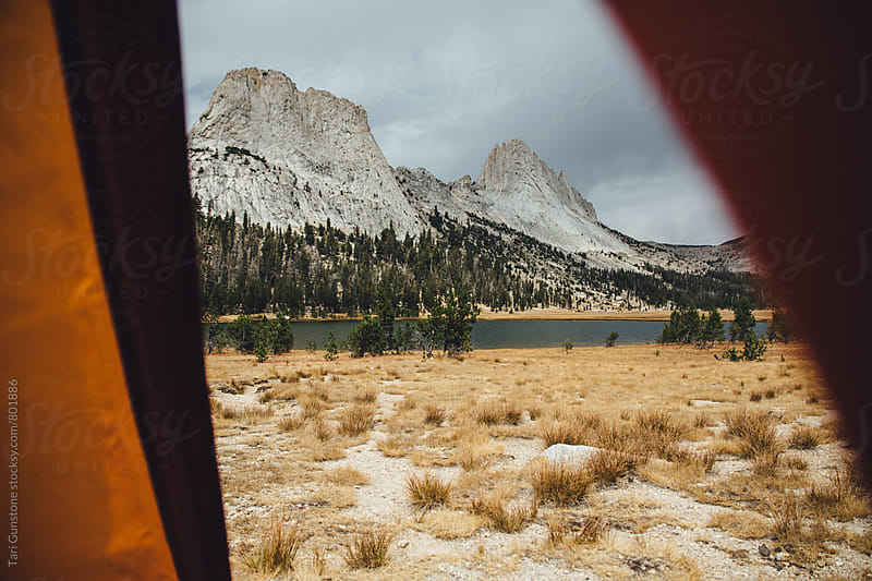 Granite peak seen through tent opening by Tari Gunstone for Stocksy United