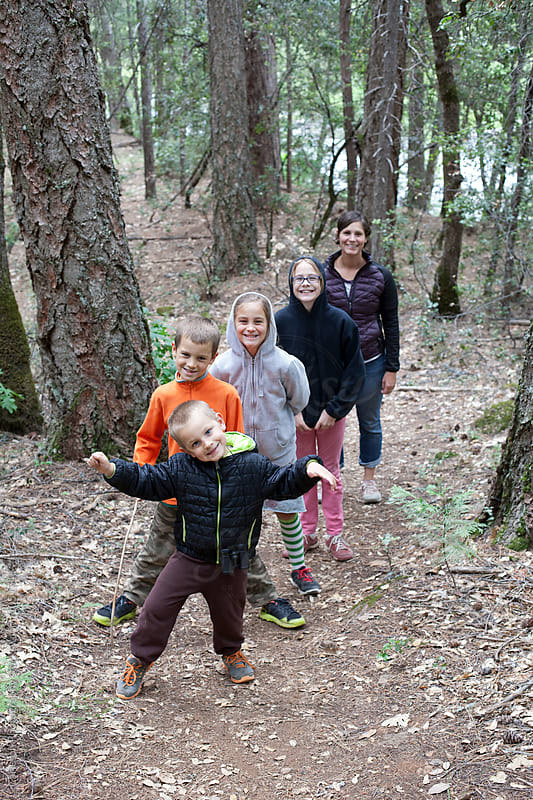 Four kids and mom hiking on a trail by Carleton Photography for Stocksy United