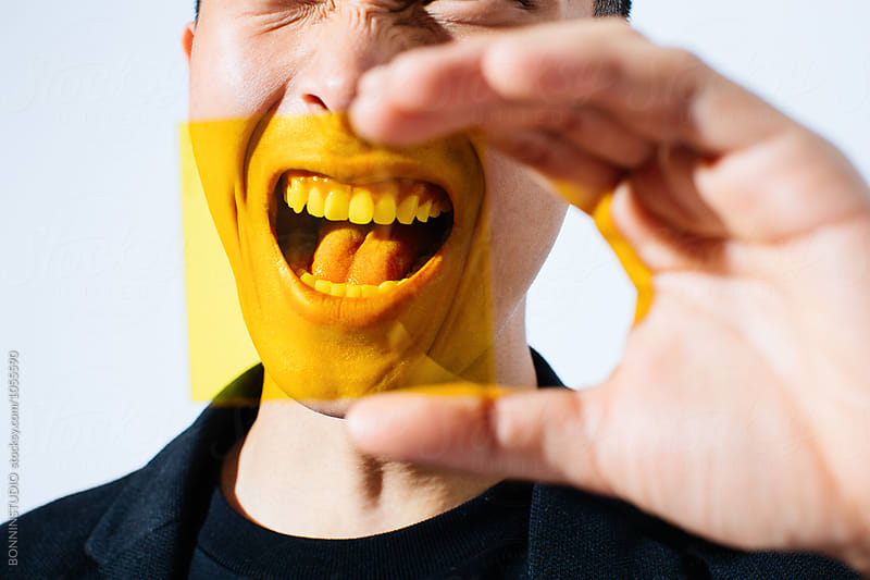 Portrait of an asian man shouting through yellow glass. by BONNINSTUDIO for Stocksy United
