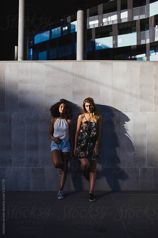 Two attractive girls leaning against a wall by michela ravasio for Stocksy United