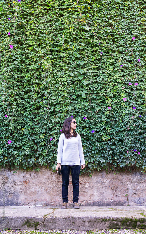 Woman posing in a vertical garden ivy by ACALU Studio for Stocksy United