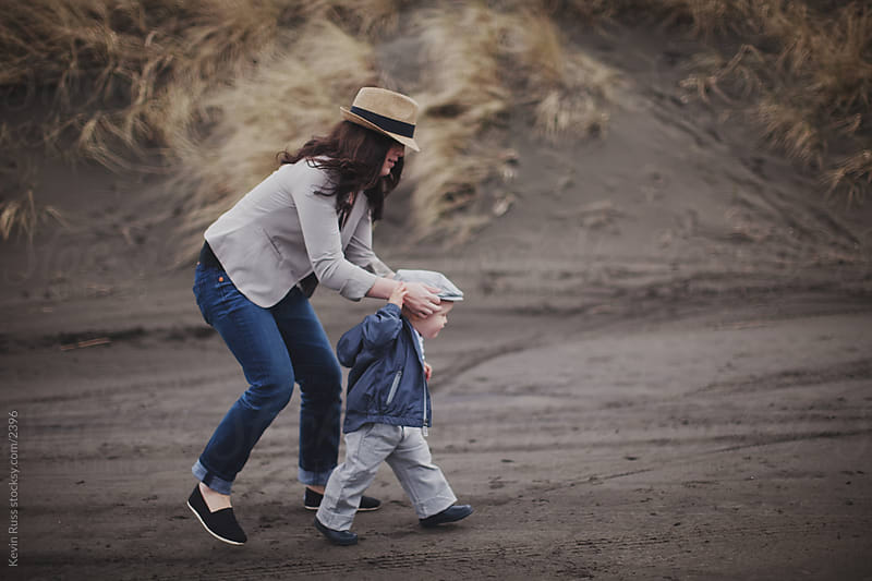 Mother Helping Son Walking at the Beach by Kevin Russ for Stocksy United