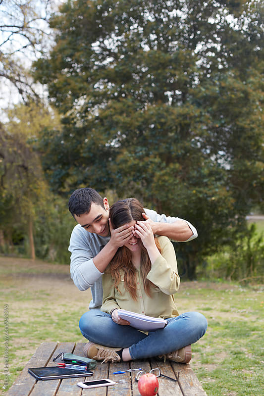 Young man covering the eyes of a young woman for a surprise by Miquel Llonch for Stocksy United