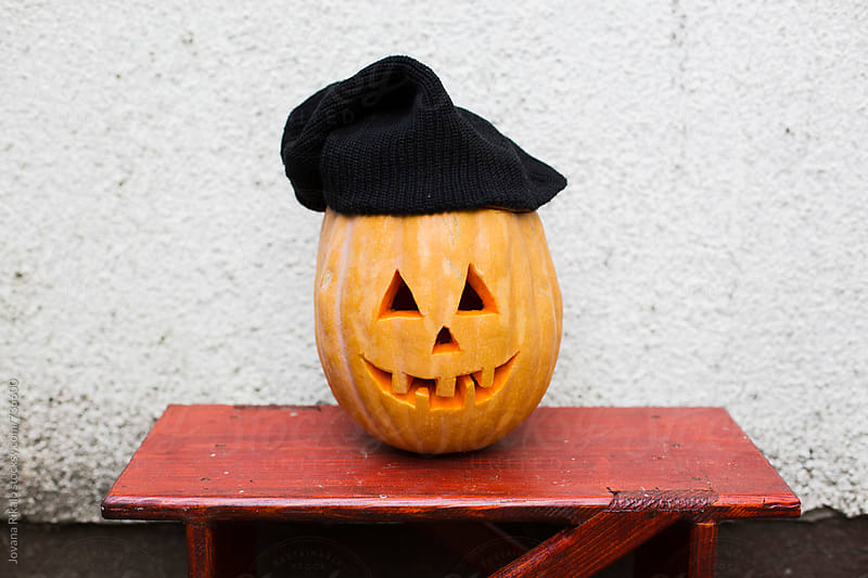 Scary pumpkin wearing a black hat by Jovana Rikalo for Stocksy United