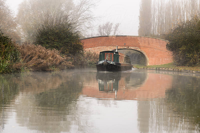Canal boat and bridge in the autumn fog by Rebecca Spencer for Stocksy United
