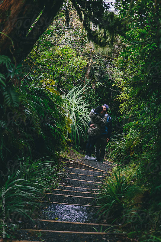 Couple kissing at secluded path in a rainforest by Andrey Pavlov for Stocksy United
