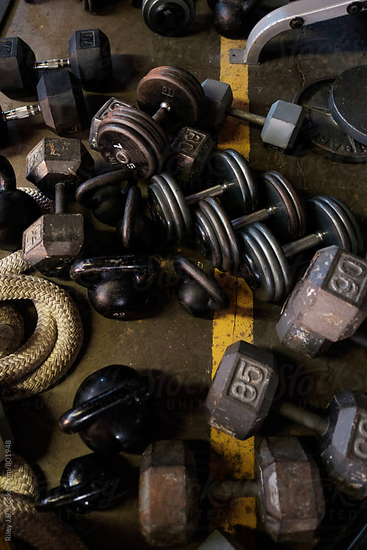 A jumble of dumbbells and kettlebells on the floor of a gym by Riley Joseph for Stocksy United