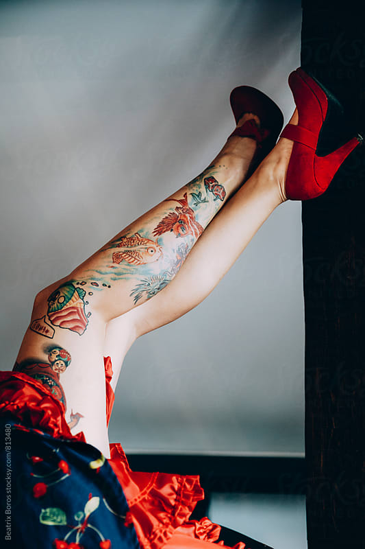 Woman's leg with full of tattoos wearing red shoes and leaning her legs upside down against a column by Beatrix Boros for Stocksy United