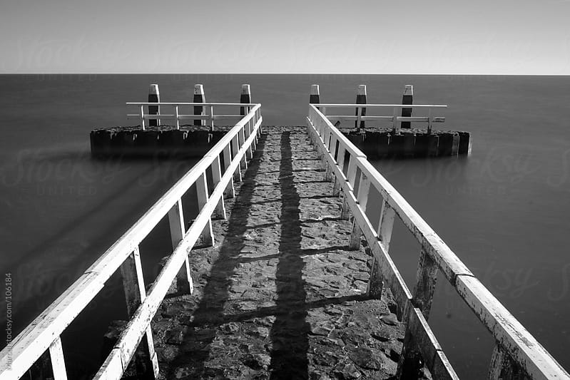 Pier at sea in black and white. by Marcel for Stocksy United