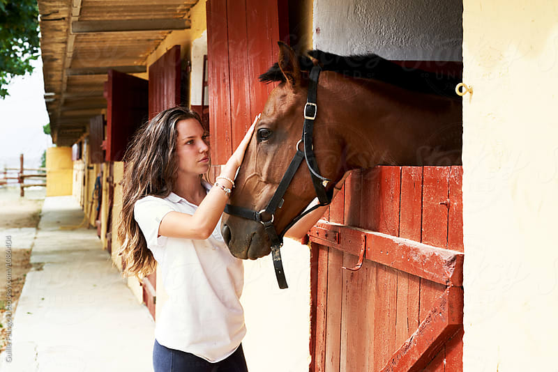 Long-haired jockey stroking her horse by Guille Faingold for Stocksy United