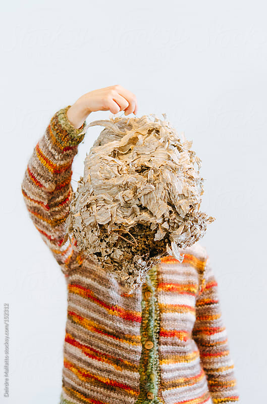 woman holding hornet's nest in front of her face by Deirdre Malfatto for Stocksy United